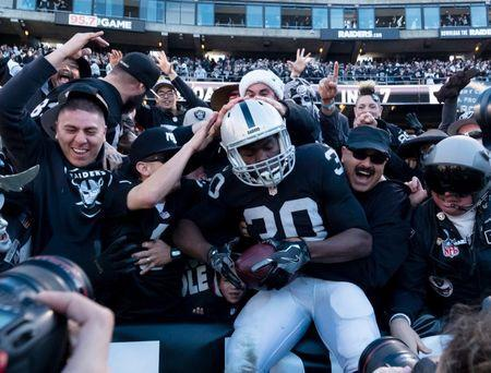 FILE PHOTO: Oakland Raiders running back Jalen Edwards (30) leaps into the stands to celebrate with fans after a touchdown against the Indianapolis Colts during the second quarter at the Oakland Coliseum. Mandatory Credit: Kelley L Cox-USA TODAY Sports