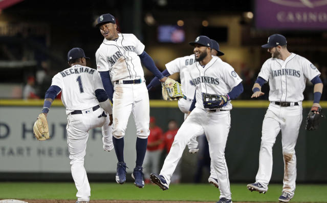 Seattle Mariners' Tim Beckham (1), Mallex Smith, Domingo Santana and Mitch Haniger celebrate after the team beat the Los Angeles Angels in a baseball game, Tuesday, April 2, 2019, in Seattle. The Mariners won 2-1. (AP Photo/Elaine Thompson)