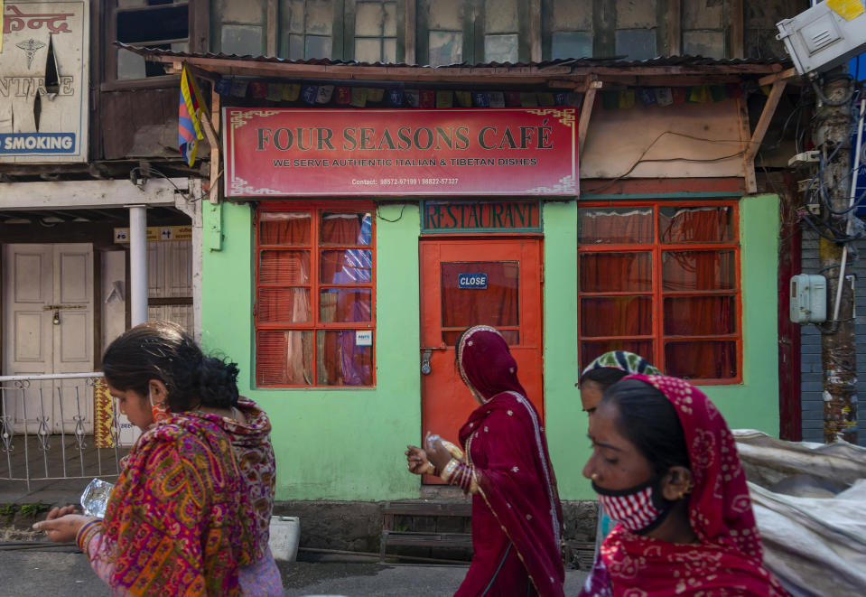 Sanitary workers, some wearing face masks as a precaution against the coronavirus, walk past a closed restaurant during lockdown imposed to curb the spread of the coronavirus in Dharmsala, India, Saturday, May 22, 2021. (AP Photo/Ashwini Bhatia)