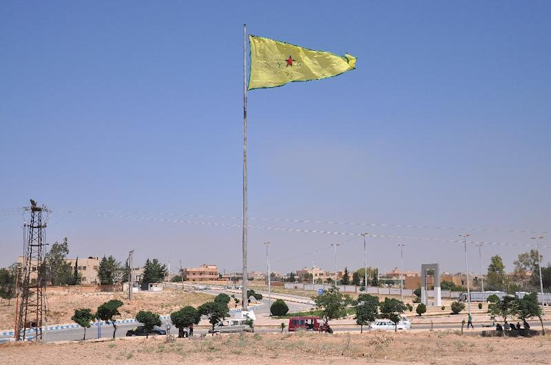 A Kurdish People's Protection Units (YPG) flag flutters above the Syrian town of Tal Abyad, on the border with Turkey, on June 25, 2015 (AFP Photo/Delil Souleiman)