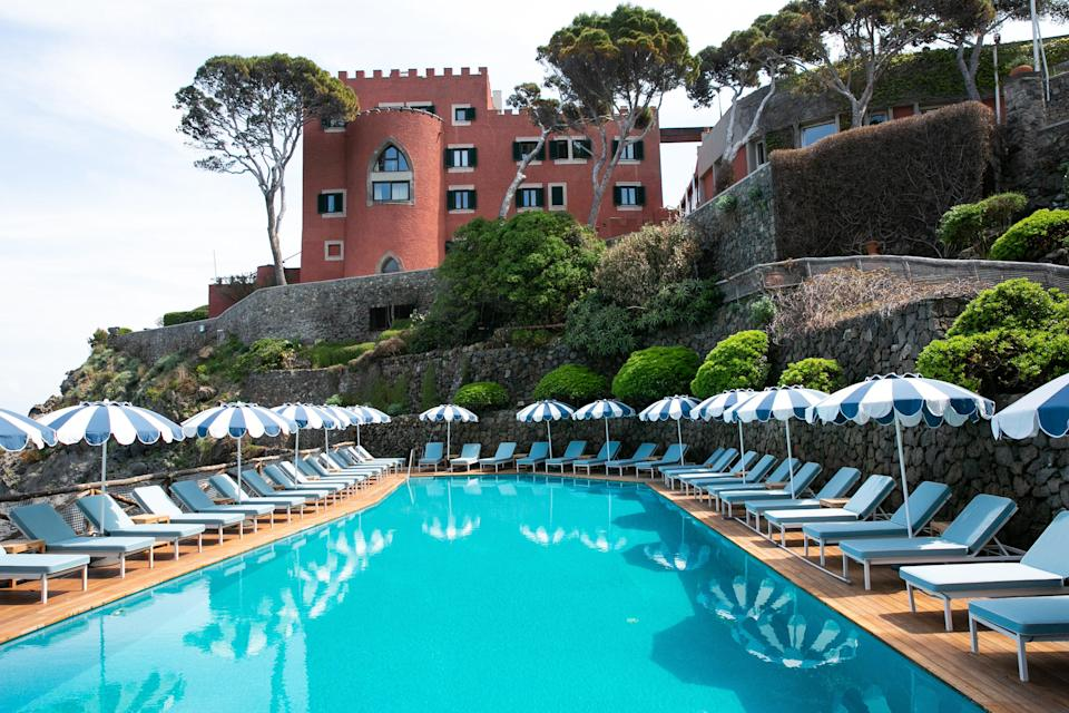 """<p><strong>Set the scene.</strong> A coastal track meanders alongside wild forest, where wood pigeons coo among the Mediterranean pines and wisteria tangles wildly about the lemon trees. Round a corner and there it is: a blood-red Aragonese castle, built as a watchtower in the 17th century and spruced up to Italian elegance, out on a rocky limb in the electrifying blue-green Gulf of Naples. Stone terraces tumble down the hillside around a fingernail of a bay, set with oversized terracotta pots of palms, seating in the nooks, Indian parasols riffling in the breeze. The suncatcher pool deck has shades of Slim Aarons, day beds dressed up in blue and white stripes.</p> <p><strong>What's the backstory?</strong> On a mission to create a third hotel, <a href=""""https://www.cntraveler.com/hotels/porto-ercole-gr/hotel-il-pellicano?mbid=synd_yahoo_rss"""" rel=""""nofollow noopener"""" target=""""_blank"""" data-ylk=""""slk:Il Pellicano's"""" class=""""link rapid-noclick-resp"""">Il Pellicano's</a> driving force Marie-Louise Sciò (CEO and creative director), spent 10 years searching la tutti Italia for a doer-upper. It had to be just right—""""a place that has a soul, and a bit of a story; the right elements that just need to be polished."""" In Ischia, she found it. """"A little bit run down but so charming, with so much potential.""""</p> <p>Mezzatorre is a tower built (or half built; literally, """"half a tower""""—typical, says one islander, of Ischians—they never finished it) as a look-out for marauding Saracen pirates. Then owned by dukes, yada yada, until centuries later, in the 1930s, it wound up as a simple hotel. One owner, writer Luigi Patalano, built a villa on the grounds, bought by film director Visconti. Then along came Pellicano Hotels in 2019, which bought the whole shebang, injecting some va-va-voom and sprucing it up to Italian diva levels.</p> <p><strong>What can we expect in our room?</strong> This being a watchtower, almost all of the rooms have magnificent views of the sea. Ceilings are vaulted, bree"""