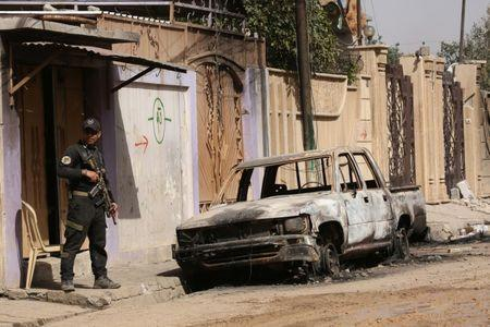 A member of the Iraqi Counter-Terrorism Service (CTS) stands next to a burnt car from clashes in the Mansour district of Mosul