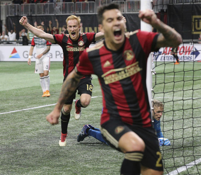 Atlanta United midfielder Jeff Larentowiz, left, and Franco Escobar react as teammate Hector Villalba scores a goal against D.C. United for a 3-0 lead in the home opener during the second half in a MLS soccer match on Sunday, March 11, 2018, in Atlanta. Atlanta United won the game 3-1. (Curtis Compton/Atlanta Journal-Constitution via AP)