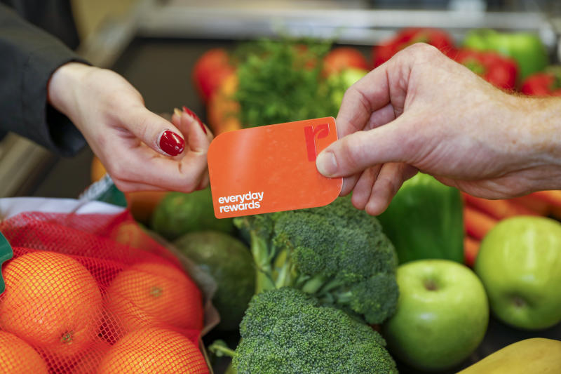 A man hands a woman a Woolworths Everyday Rewards card in front of fruit and vegetables.