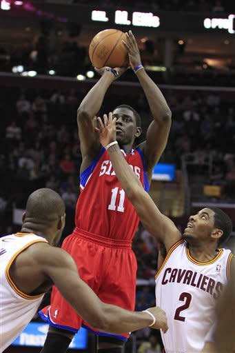 Philadelphia 76ers' Jrue Holiday (11) shoots over Cleveland Cavaliers' Kyrie Irving (11) and Antawn Jamison in the first quarter in an NBA basketball game Wednesday, April 18, 2012, in Cleveland. Holiday scored a team-high 24 points as the 76ers won 103-87. (AP Photo/Tony Dejak)