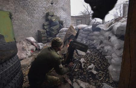Ukrainian serviceman fires grenade launcher at his position on front line at industrial zone of Avdiyivka
