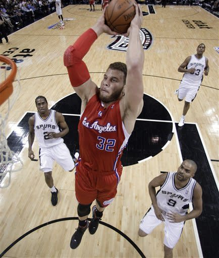 Los Angeles Clippers' Blake Griffin (32) soars to the basket past San Antonio defenders Tony Parker (9), of France, Kawhi Leonard (2) and Boris Diaw (33), of France, during the first quarter of Game 1 of an NBA basketball Western Conference semifinal playoff series, Tuesday, May 15, 2012, in San Antonio. (AP Photo/Eric Gay)