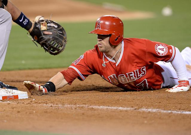 Los Angeles Angels' Collin Cowgill dives back to first base to beat the throw by New York Yankees pitcher Hiroki Kuroda, of Japan, during the fifth inning of a baseball game in Anaheim, Calif., Tuesday, May 6, 2014. (AP Photo/Jayne Kamin-Oncea)