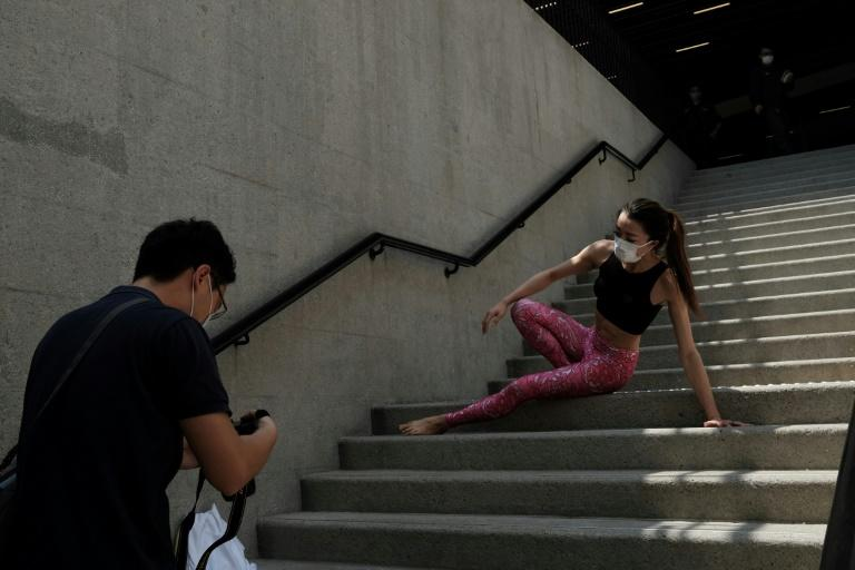 A woman wearing a face mask poses for photos while performing a yoga in central Hong Kong