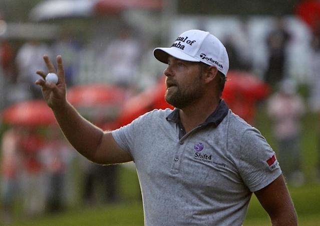Ryan Moore of the U.S. acknowledges the crowd after making a putt on the 18th green during the final round of the CIMB Classic golf tournament at the Kuala Lumpur Golf and Country Club in Kuala Lumpur, Malaysia, Sunday, Oct. 27, 2013. Moore and his compatriot Gary Woodland finished tied for the lead after the final round of the tournament on Sunday, with the sudden-death playoff postponed until Monday due to darkness. (AP Photo/Lai Seng Sin)