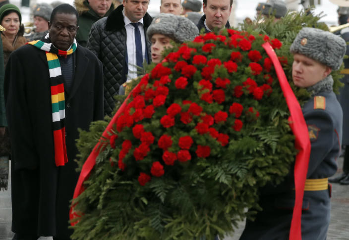 Zimbabwe's President Emmerson Mnangagwa, left, attends a wreath laying ceremony at the Tomb of the Unknown Soldier in Moscow, Russia, Tuesday, Jan. 15, 2019. The president of Zimbabwe, whose country is facing its worst economic crisis in a decade, is visiting Russia in hopes of securing long-term loans. (Sergei Ilnitsky/Pool Photo via AP)