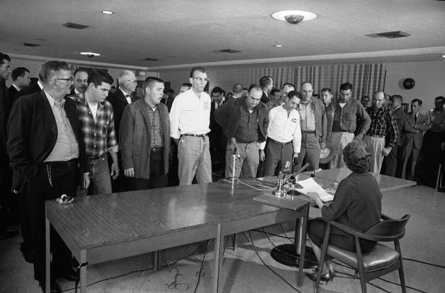 <p>Eighteen defendants stand before Miss Esther Carter (seated) as they were arraigned with the slaying of thee Civil Rights workers on Dec. 4, 1964 in Mississippi. (Photo: HWC/AP) </p>