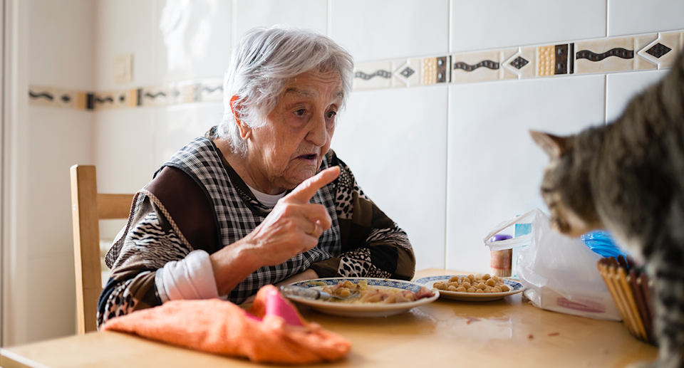 An elderly lady sitting at the table and talking to a cat.