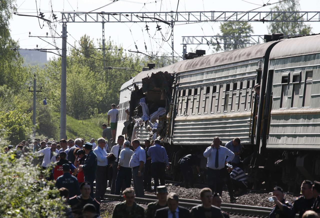 People gather near a passenger train damaged in a collision with a freight train in Moscow region May 20, 2014. The passenger train on its way to Moldova collided with a freight train near Moscow on Tuesday, killing at least four people and injuring 15, a spokeswoman for Russia's Emergencies Ministry said. The reason for the collision, near the town of Naro-Fominsk 55 km (34 miles) southwest of Moscow, was not immediately clear. REUTERS/Grigory Dukor (RUSSIA - Tags: DISASTER TRANSPORT)
