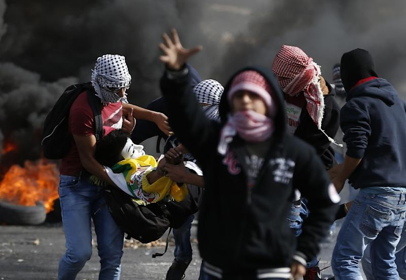 Palestinian protesters carry a wounded person wearing a mask during clashes with Israeli troops in the Israeli-occupied West Bank on November 11, 2015 (AFP Photo/Abbas Momani)