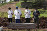 An Islamic cleric leads relatives in prayer during the burial of a man in the special section of Jombang Public Cemetery reserved for those who died of COVID-19, in Tangerang on the outskirts of Jakarta, Indonesia, Monday, June 21, 2021. Indonesia saw significant spikes in confirmed COVID-19 cases recently, an increase blamed on travel during last month's Eid al-Fitr holiday as well as the arrival of new virus variants, such as the the Delta version first found in India. (AP Photo/Tatan Syuflana)