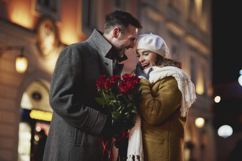 Man giving his amazed girlfriend bunch of red roses on Valentine's Day