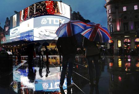 People stand under Union Flag umbrellas during rain in Piccadilly Circus in London