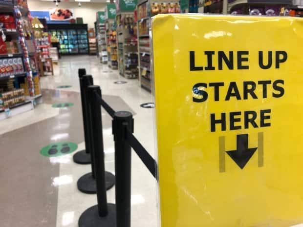 A sign directs shoppers in a grocery store in Toronto. Unions are seeking clarity from the Ontario government as to whether their members are considered essential under Phase 2 of the province's COVID-19 rollout. (Jonathan Castell/CBC - image credit)