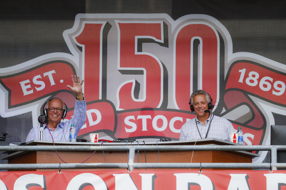 Cincinnati Reds radio announcer Marty Brennaman, left, waves next to his son Thom, in a special outside booth before the Reds' baseball game against the Milwaukee Brewers, Wednesday, Sept. 25, 2019, in Cincinnati. (AP Photo/John Minchillo)