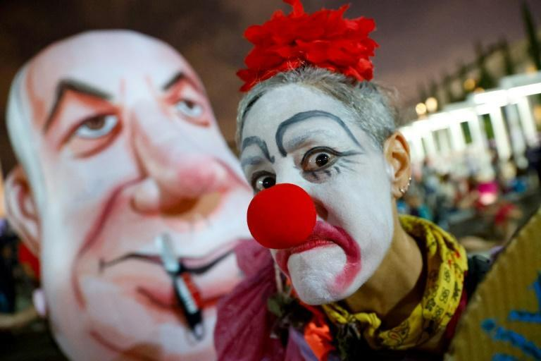 An Israeli woman in a clown outfit mocks a giant head costume representing Prime Minister Benjamin Netanyahu as she takes part in a demonstration in Tel Aviv against the government and an imminent and unprecedented second nationwide virus lockdown