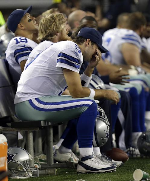 Dallas Cowboys quarterback Tony Romo sits on the bench in the final minutes of the second half of an NFL football game against the Green Bay Packers, Sunday, Dec. 15, 2013, in Arlington, Texas. Romo threw two interceptions in the game's final three minutes. The Green Bay Packers rallied from a 23-point halftime deficit to beat the Cowboys. (AP Photo/Tim Sharp)