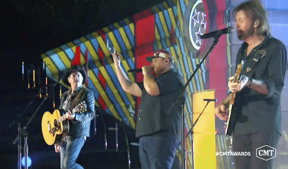 "In this video image provided by CMT, Kix Brooks, from left, Luke Combs and Ronnie Dunn perform ""1, 2 Many"" during the Country Music Television awards airing on Wednesday Oct. 21, 2020. (CMT via AP)"