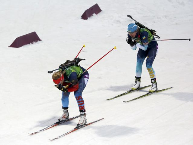 Russia's Olga Zaitseva (L) and Ukraine's Juliya Dzhyma ski during the women's biathlon 4 x 6 km relay event at the Sochi 2014 Winter Olympic Games in Rosa Khutor February 21, 2014. REUTERS/Stefan Wermuth (RUSSIA - Tags: SPORT BIATHLON OLYMPICS)