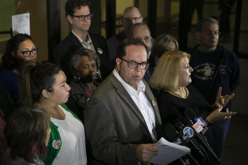 United Teachers Los Angeles union president Alex Caputo-Pearl, center, speaks during a news conference at the Los Angeles Unified School District headquarters Wednesday, Jan. 9, 2019, in Los Angeles. The union representing teachers in Los Angeles, the nation's second-largest school district, postponed the start of a strike until Monday because of the possibility of a court-ordered delay of a walkout. (AP Photo/Jae C. Hong)