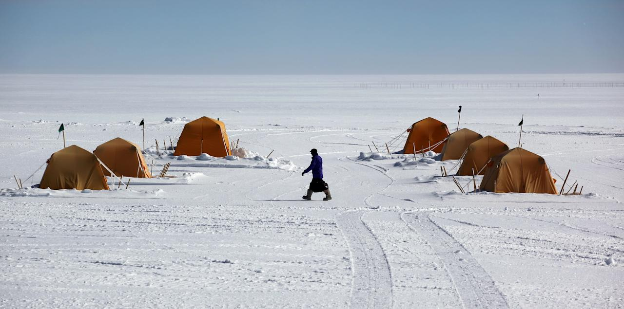 In this July 15, 2011 photo, a man walks past sleeping tents at Summit Station, a remote research site operated by the U.S. National Science Foundation, (NSF), situated 10,500 feet above sea level, on top of the Greenland ice sheet. Across Greenland's vast white landscape, teams of researchers from around the world are searching for clues to the potential effects of global warming on Greenland's ice. (AP Photo/Brennan Linsley)