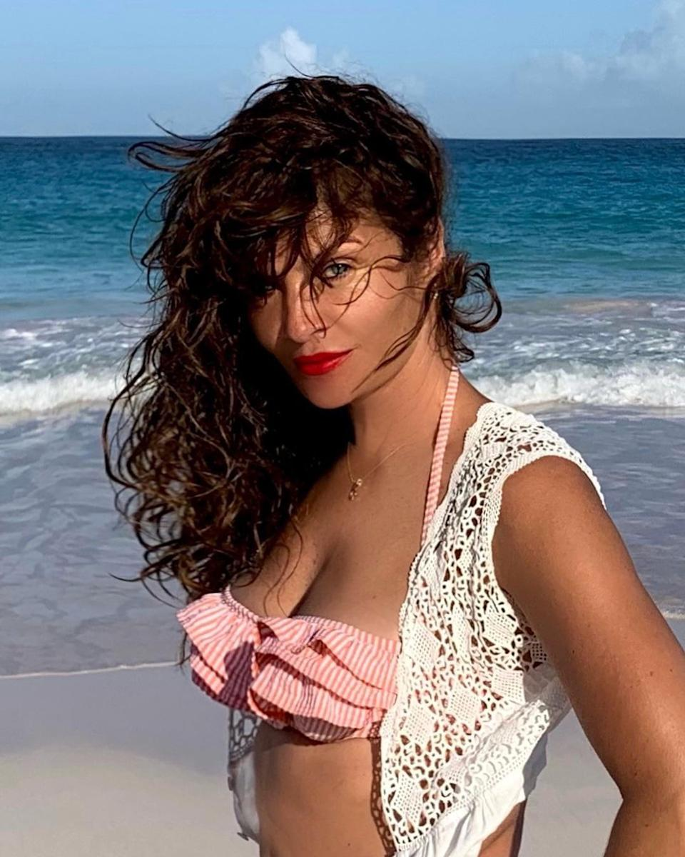 Helena Christensen with her hair to one side on a beach