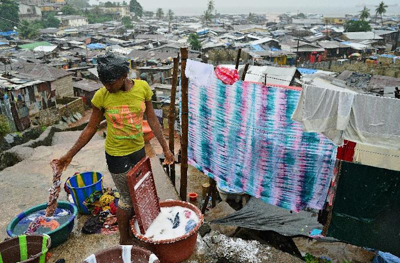 A woman is seen washing clothes in the Kroo Bay slum in Freetown, Sierra Leone, on August 13, 2014 (AFP Photo/Carl de Souza)