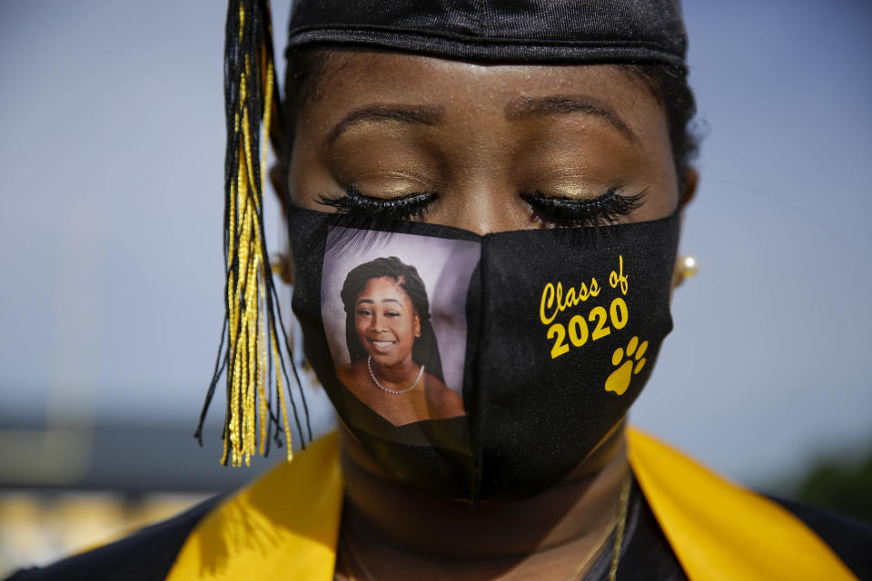 FILE - In this May 15, 2020, file photo, a graduating senior Yasmine Protho, 18, wears a photo of herself and Class of 2020 on her protective mask amid the coronavirus pandemic as she graduates with only 9 other classmates at a time with limited family attending at Chattahoochee County High School in Cusseta, Ga. (AP Photo/Brynn Anderson, File)