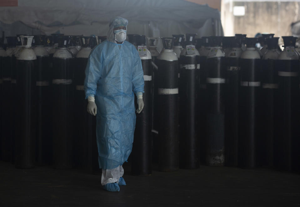 A front-line worker passes oxygen ciylinders at the Steve Biko Academic Hospital's outside parking area in Pretoria, South Africa, Monday, Jan. 11, 2021. As the numbers of new confirmed cases rise, South Africa's hospitals are exceeding capacity, according to health officials (AP Photo/Denis Farrell)