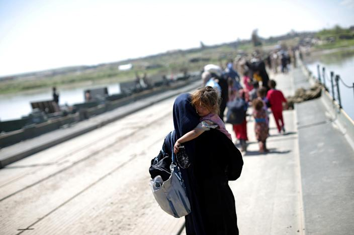An Iraqi woman carries a girl across a pontoon bridge over the Tigris River south of Mosul, Iraq. (Photo: Andres Martinez Casares)
