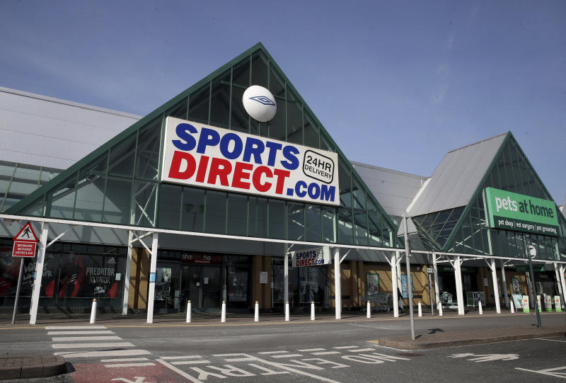 A view of a closed Sports Direct store next to an open Pets at Home store, the day after Prime Minister Boris Johnson put the UK in lockdown to help curb the spread of the coronavirus. Sports Direct has said it will close its stores in a major U-turn after initially calling for its workers to continue selling essential sports and fitness equipment in the face of the coronavirus outbreak, in Telford, England, Tuesday March 24, 2020. For some people the COVID-19 coronavirus causes mild or moderate symptoms, but for others it causes severe illness. (Nick Potts / PA via AP)