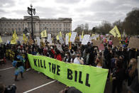 Demonstrators holding banners and flags march past Buckingham palace during a 'Kill the Bill' protest in London, Saturday, April 3, 2021. The demonstration is against the contentious Police, Crime, Sentencing and Courts Bill, which is currently going through Parliament and would give police stronger powers to restrict protests. (AP Photo/Matt Dunham)