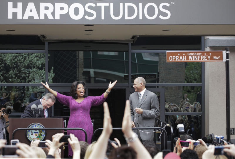 "File-This May 11, 2011, file photo shows talk-show host Oprah Winfrey reacting after a street outside her Harpo Studios in Chicago was proclaimed ""Oprah Winfrey Way"" during a ceremony with Chicago Mayor Richard M. Daley, left, and Bobby Ware, commissioner of the Chicago Department of Transportation. Winfrey is selling Harpo Studios in Chicago to a developer, but the studio will remain on the property for another two years. Harpo Inc. said in a statement that it has entered into a purchasing agreement with Sterling Bay Cos. for the four-building campus on Chicago's West Side. (AP Photo/M. Spencer Green,File)"
