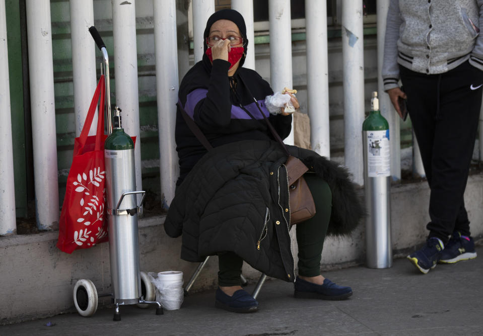 A woman takes her place as she waits to refill an oxygen tank for a family member sick with COVID-19 in the Iztapalapa district of Mexico City, Tuesday, Jan. 26, 2021. The city is offering free oxygen refills for COVID-19 patients. (AP Photo/Marco Ugarte)