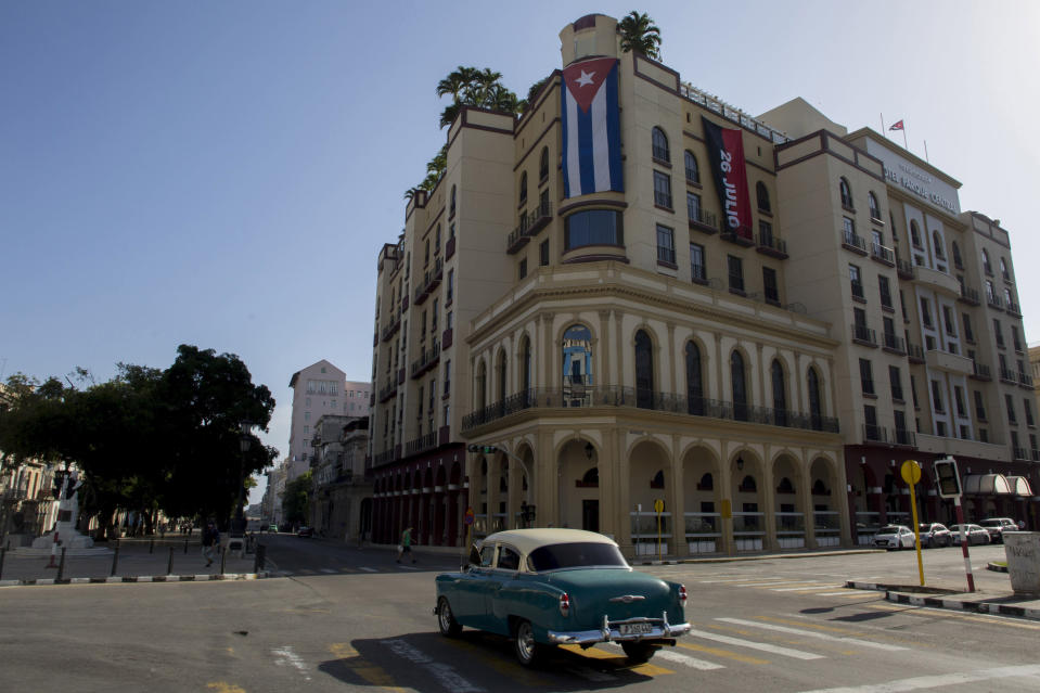A Cuban flag hangs on Parque Central Hotel in Havana, Cuba, early Monday, July 12, 2021, the day after protests against food shortages and high prices amid the coronavirus crisis. (AP Photo/Ismael Francisco)