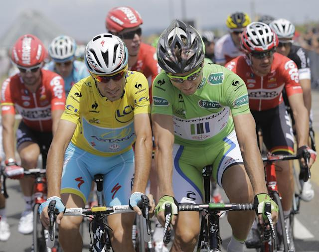 Italy's Vincenzo Nibali, wearing the overall leader's yellow jersey, and Peter Sagan of Slovakia, wearing the best sprinter's green jersey, ride shoulder-to-shoulder during the ceremonial procession prior to the start of the fourth stage of the Tour de France cycling race over 163.5 kilometers (101.6 miles) with start in Le Touquet and finish in Lille, France, Tuesday, July 8, 2014. (AP Photo/Laurent Cipriani)