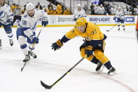 Nashville Predators right wing Viktor Arvidsson (33) moves the puck against Tampa Bay Lightning's Ben Thomas (56) in the second period of an NHL hockey game Saturday, April 10, 2021, in Nashville, Tenn. (AP Photo/Mark Humphrey)