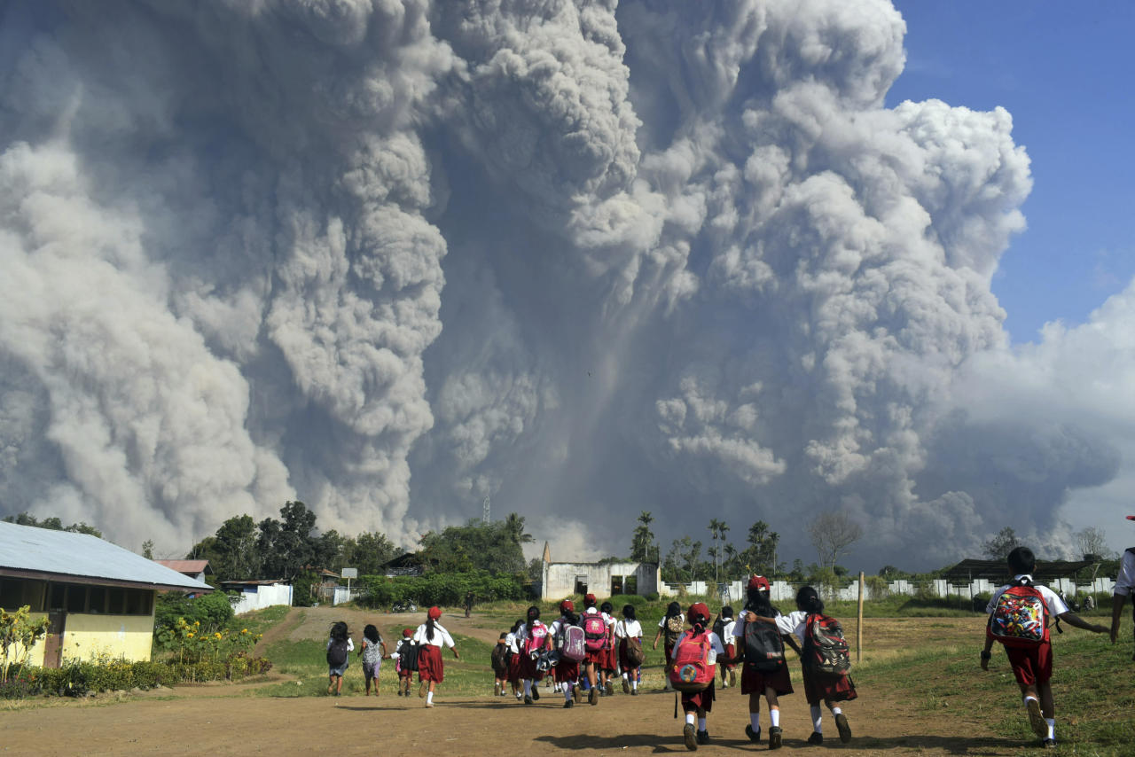 In this Monday, Feb. 19, 2018, file photo, school children walk as Mount Sinabung erupts in Karo, North Sumatra, Indonesia. Rumbling Mount Sinabung on the Indonesian island of Sumatra has shot billowing columns of ash more than 5,000 meters (16,400 feet) into the atmosphere and hot clouds down its slopes.  The volcano, one of three currently erupting in Indonesia, was dormant for four centuries before exploding in 2010. (AP Photo/Sarianto, File)