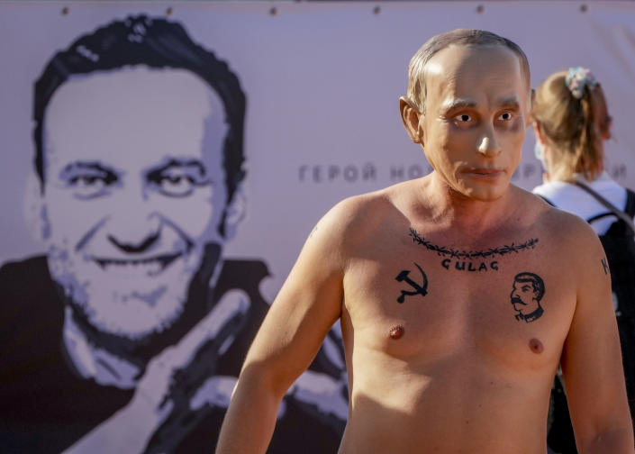 A man wearing a Vladimir Putin mask takes part in a demonstration for imprisoned Alexei Navalny, poster at left, in Geneva, Switzerland Tuesday, June 15, 2021. US President Joe Biden and Russia President Vladimir Putin will meet for talks in Geneva on Wednesday. (AP Photo/Michael Probst)