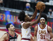 Cleveland Cavaliers guard Collin Sexton, right, shoots over Portland Trail Blazers center Enes Kanter during the first half of an NBA basketball game in Portland, Ore., Friday, Feb. 12, 2021. (AP Photo/Craig Mitchelldyer)