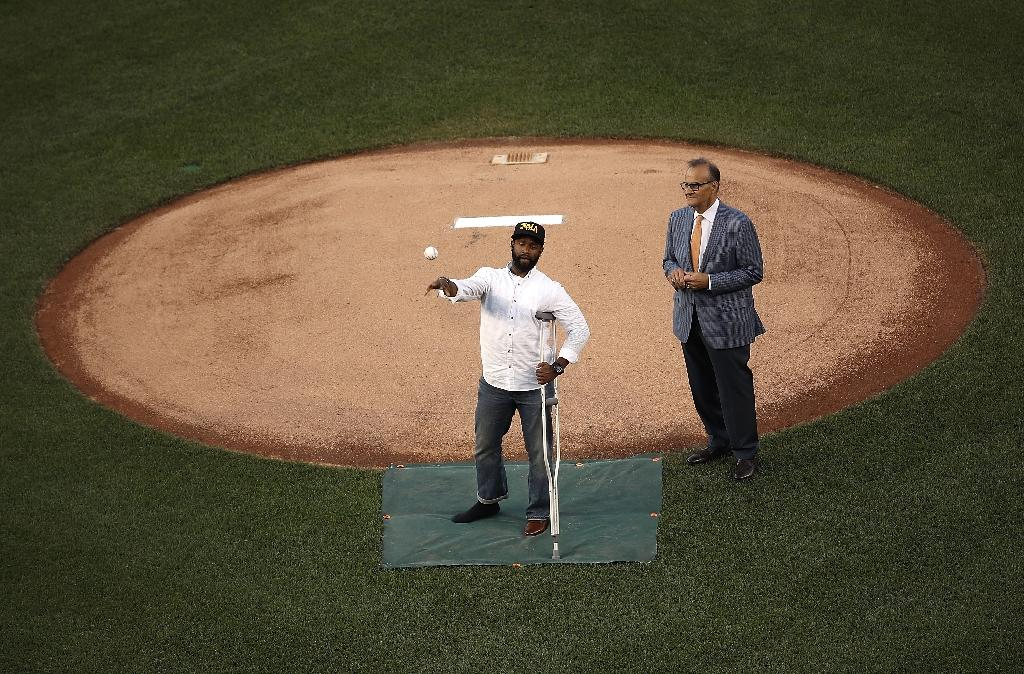 U.S. Capitol Hill special agent David Bailey (L), who was wounded in yesterday's shooting, throws out the first pitch at the Congressional Baseball Game in Washington, DC (AFP Photo/WIN MCNAMEE)