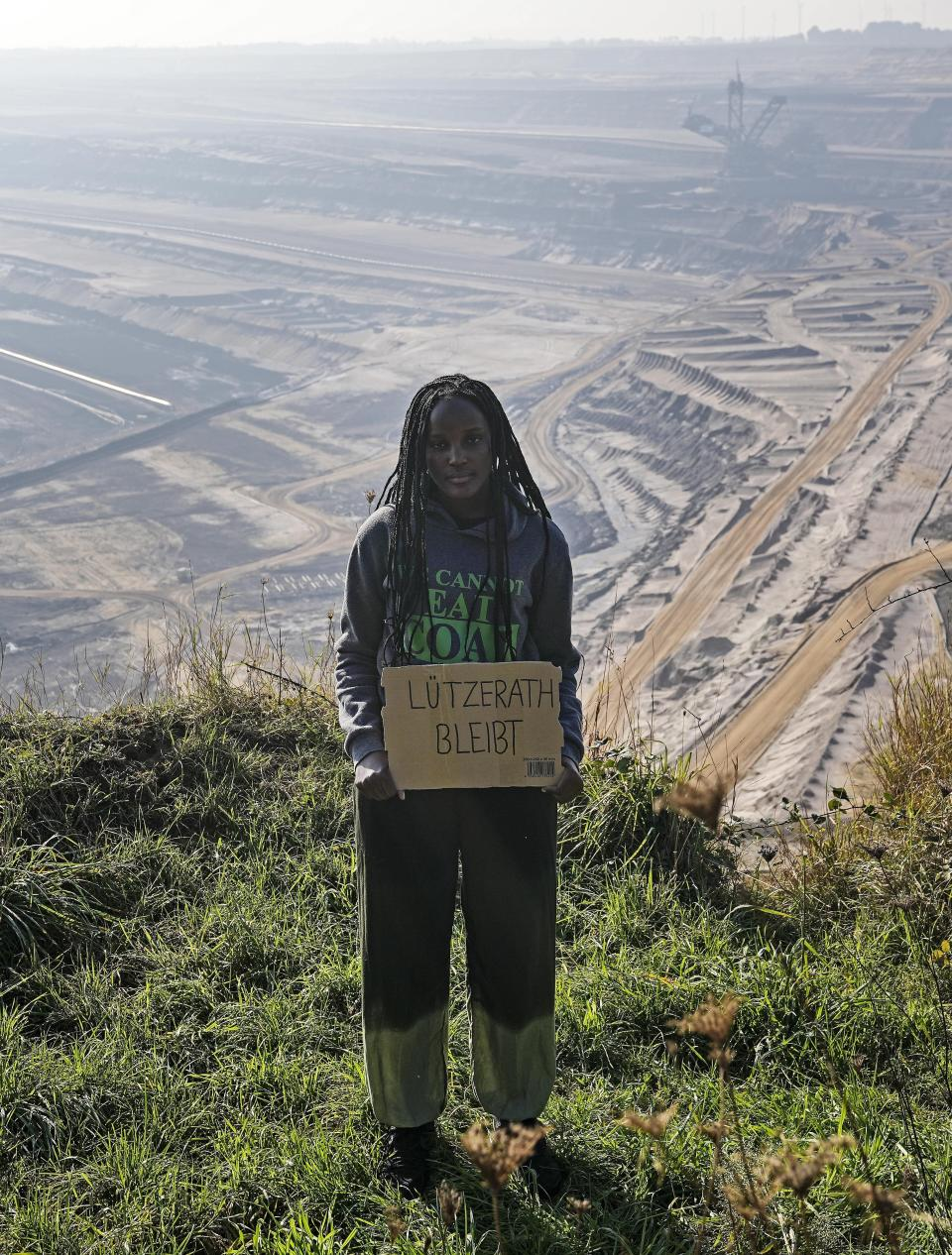 """Climate activist Vanessa Nakate from Uganda holds a sign that reads: """"Luetzerath stays"""" during a visit to the Garzweiler open-cast coal mine in Luetzerath, western Germany, Saturday, Oct. 9, 2021. The village of Luetzerath, now almost entirely abandoned as the mine draws ever closer, will be the latest village to disappear as coal mining at the Garzweiler mine expands. Garzweiler, operated by utility giant RWE, has become a focus of protests by people who want Germany to stop extracting and burning coal as soon as possible. (AP Photo/Martin Meissner)"""