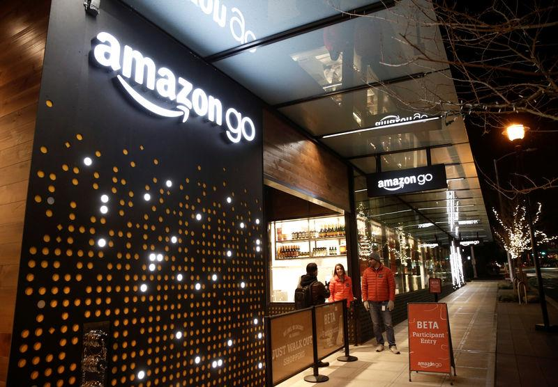 Amazon employees are pictured outside the Amazon Go brick-and-mortar grocery store without lines or checkout counters, in Seattle Washington