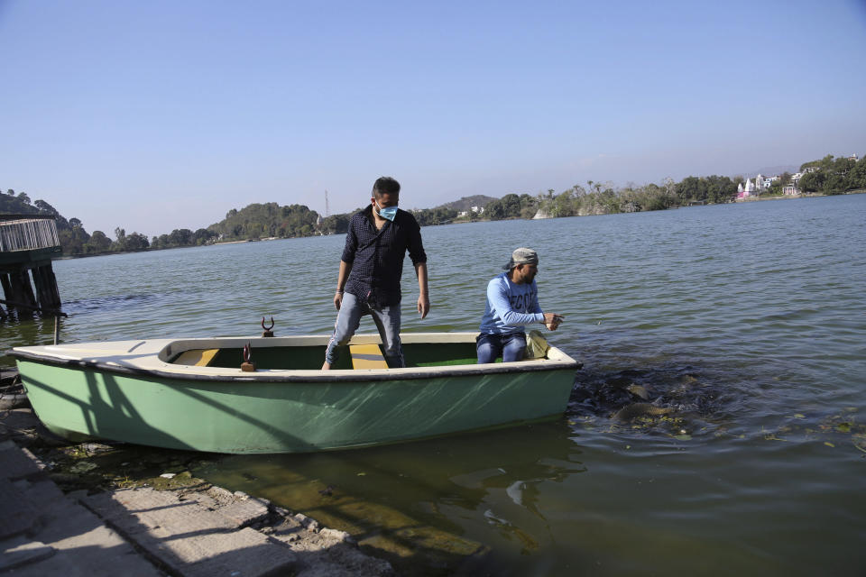 Tourists feed fish at Surinsar Lake on the outskirts of Jammu, India, Wednesday, March 3, 2021. (AP Photo/Channi Anand)