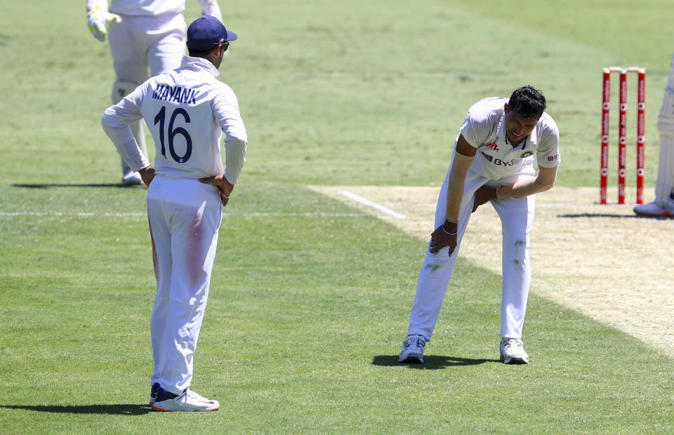 India's Navdeep Saini, right, reacts after injuring his leg while bowling during play on the first day of the fourth cricket test between India and Australia at the Gabba, Brisbane, Australia, Friday, Jan. 15, 2021. (AP Photo/Tertius Pickard)